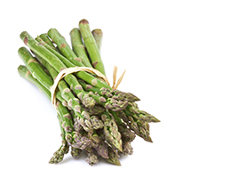 A bundle of asparagus, bound by a rubber band, sits against a white background.